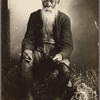 Studio portrait of seated man with long beard.