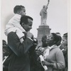 Harry Belafonte holds his son David on his shoulders while talking to visitors on Liberty Island, New York