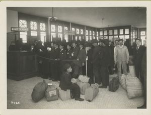 Ready for travel and going north, south and west. Immigrants with baggage lined up at teller's windows marked money exchange.