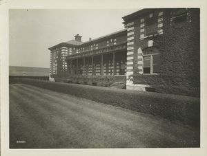Exterior of Ellis Island building, showing ivy-covered wall, porch and balcony with flower boxes, well-kept lawn and hedge.