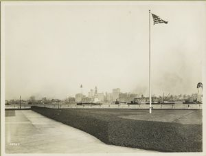 View of the New York skyline from Ellis Island. The Woolworth Building (the tallest building, at left) is under construction, which dates the photograph as c. 1912-13.