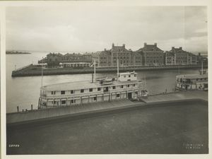 View of Ellis Island buildings and two ferries at pier; apparently taken from atop the Immigration Station building.