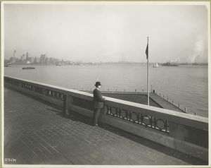 A derby-topped gentleman observing the harbor form the observation roof on one wing of the Immigration Station. The gentleman is possibly William Williams, Commissioner of Immigration at Ellis Island form 1902-5 and 1909-13, from whose estate these photographs came. The New York skyline, showing the nearly-completed Woolworth Building tower, is at the left.
