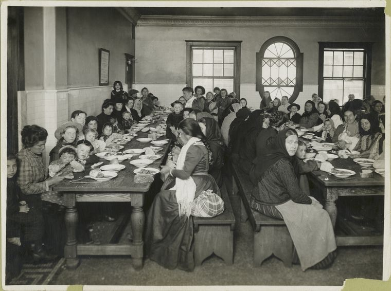 "An early-20th century photo by Edwin Levick, ""Uncle Sam, host. Immigrants being served a free meal at Ellis Island,"" is part of the NYPL's photography collection."