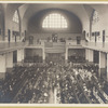 Immigrants seated on long benches, Main Hall, U.S. Immigration Station
