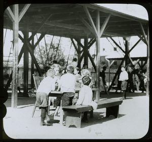 Corlear's Hook Park : boys and girls around table, swings beyond, ca. 1910s.