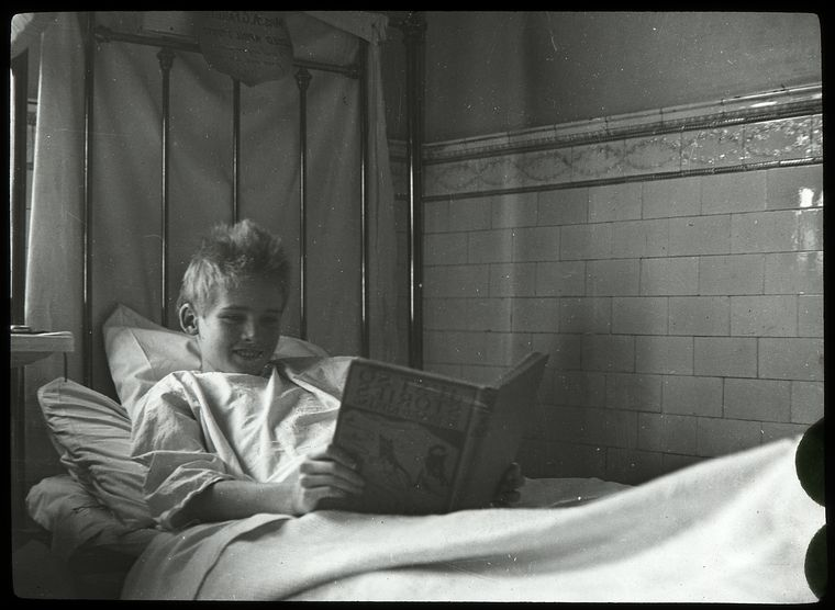 Post Graduate Hospital : boy reading Just so stories in bed, 1923.