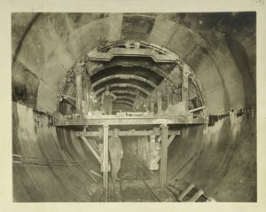 Rondout pressure tunnel. Steel arch forms mounted on traveler with plates removed to permit placing of concrete in haunches. Contract 12. October 10, 1910.