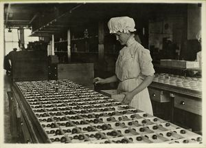 [Woman in a mob cap sorting chocolates into wooden boxes.]