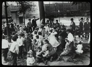 Work with schools, Hudson Park Branch : men look on as children are read to in the park, ca. 1910.