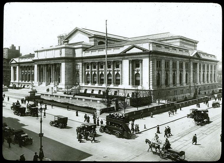 Central building, exterior views, Fifth Avenue : above Fifth Ave. and 42nd Street, looking southwest, library wagons, double-decker bus, cars, ca. 1910s? or 1920s?