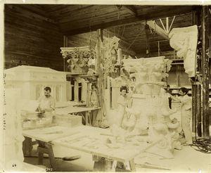 [Plaster workshop : men working on a model of a Corinthian capital.]