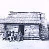 Slaves in front of a cabin.