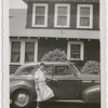 Opera singer Ellabelle Davis posing with a car in front of her home