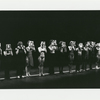 Cast members in line on stage holding headshots in front of their faces in the stage production of A Chorus Line.