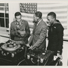 Bugler Leonard Madden (left) and sailor Clarence Brooks (right) record talking letter records to families at Chappie Willet Recording Studios, New York City, with a Willet arranger, circa 1942