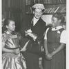 Actress Rosalind Russell, with two students from the St. Charles Parochial School, attending the Second Annual Tea of the St. Charles Women's Auxiliary, held at the Duchesne Residence School, in New York City, in May 1953. Ms. Russell, with three others, received awards for their contributions in the field of Human Relations