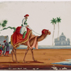 Camel and rider in white robe, with two white buildings and figures standing in the background