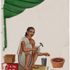 Seated male silversmith/jewelrymaker with small jewellry on red rug, holding tools