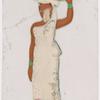 Woman in white sari carrying green bundle on head