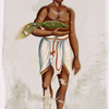 Man in white dhoti and red hat, carrying flat basket of greens in arm
