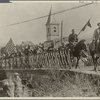 """American troops marching across a bridge"""