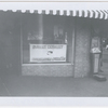 Exterior view of local Student Nonviolent Coordinating Committee headquarters in unidentified location, with sign bearing group's name and SNCC posters displayed in the window, circa early 1960s.