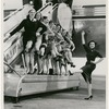 Nora Kaye and a group of female dancers of American Ballet Theatre posing in front of a plane at Idlewild Airport, 1958, no. 17