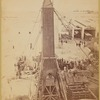 "The crated obelisk ""Cleopatra's Needle"" secured by ropes to machinery prior to being lowered to a horizontal position"