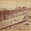 """The obelisk """"Cleopatra's Needle,"""" not yet crated, on ramp in dry dock prior to being loaded onto ship """"Dessoug"""""""