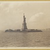 Statue of Liberty from the harbor with view of Ellis Island