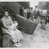 Woman with a baby sitting outside of building from which they had been evicted, in Harlem, New York