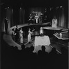 Godfrey Cambridge (in mask at table) and cast in the stage production The Blacks