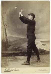 [Unidentified baseball player in dark uniform - catching form.]
