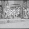 Children behind playground fence with teacher