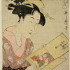 Large head and bust of a woman looking at a doll dressed to represent a boy dancing the Lion Dance (Shishi Odori)
