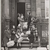 Family with packages in front of residential building (England?)