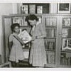"Librarian Augusta Baker showing a copy of Ellen Tarry's ""Janie Belle"" to a young girl at the library"