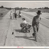 Family walking on highway, five children. Started from Ioabel, Oklahoma. Bound for Krebs, Oklahoma. Pittsburg County, Oklahoma. In 1936 the father farmed on thirds and fourths at Eagleton, McCurtain County, Oklahoma.
