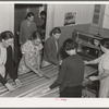 In the sewing room, migrant women are instructed in rug-making. Shafter camp for migrants (Farm Security Administration-FSA), California