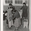 Camper receives help in fitting a coat from Works Progress Administration (WPA) sewing instructor. Shafter camp for migratory agricultural workers (Farm Security Administration-FSA), California.