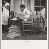 Near Douglas, Georgia. Sharecroppers grade the cured leaves on the porches and sort them to go to the tobacco auction.