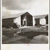 """United States government camp for migrants (Farm Security Administration), Farmersville, California. Prefabricated steel dwellings """"one step up from a tent"""" replace the use of tents in the newer California camps."""