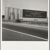 Between Tulare and Fresno on U.S. 99. Highway gas tanks and signboard approaching town. See general caption