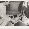 Tulare County, California. Farm Security Administration (FSA) camp for migratory agricultural workers at Farmersville. Nurse of Agricultural Workers' Health and Medical Association attends sick migrant woman while awaiting doctor