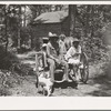 Colored sharecropper and his children about to leave home through the pine woods after their morning work at the tobacco farm stringing and putting up tobacco. Shoofly, Granville County, North Carolina