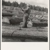 """Pond monkey"" steers log raft in mill pond. Keno, Klamath County, Oregon. General caption number 61"