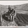 Young farmer plowing while other co-op members work in the sawmill. The tractor does work for five member families. Ola self-help sawmill co-op. Gem County, Idaho.