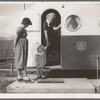 Young mother brings her child to the trailer clinic on the day when the doctor will be in camp to examine some of the children. FSA (Farm Security Administration) mobile camp. Merrill, Klamath County, Oregon