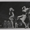 Three female dancers perform a step, while in the background male dancers as the Jets assume a menacing pose in a scene from the film version, no. 30